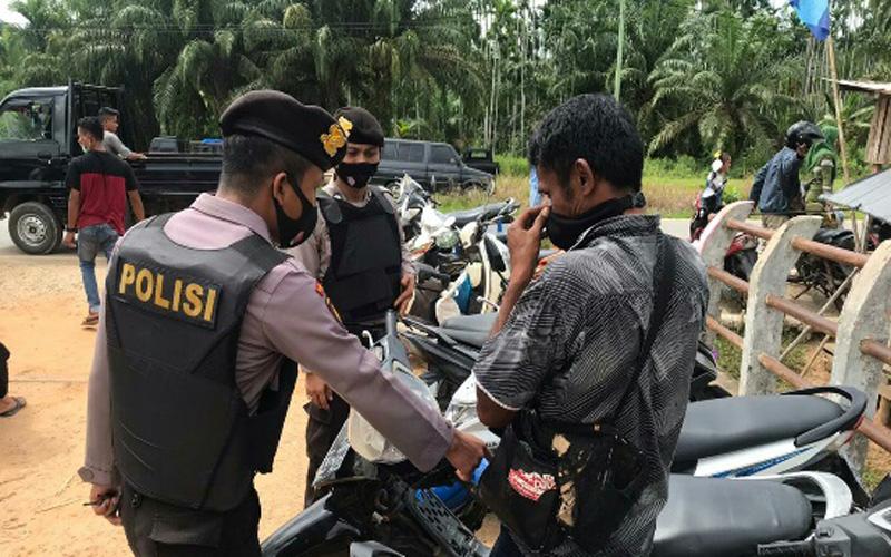 Personel Polres Rohil saat melakukan sosialisasi Prokes ke masyarakat.